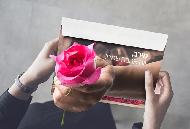 אישה מחזיקה מעטפה. יד של גבר פורצת מתוך המעטפה ומגישה לה ורד. על המעטפה הכיתוב: ״מירב, יום אהבה שמח!״